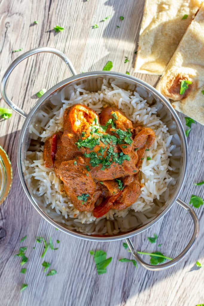 Chicken Tikka Masala and Naan bread in a metal dish