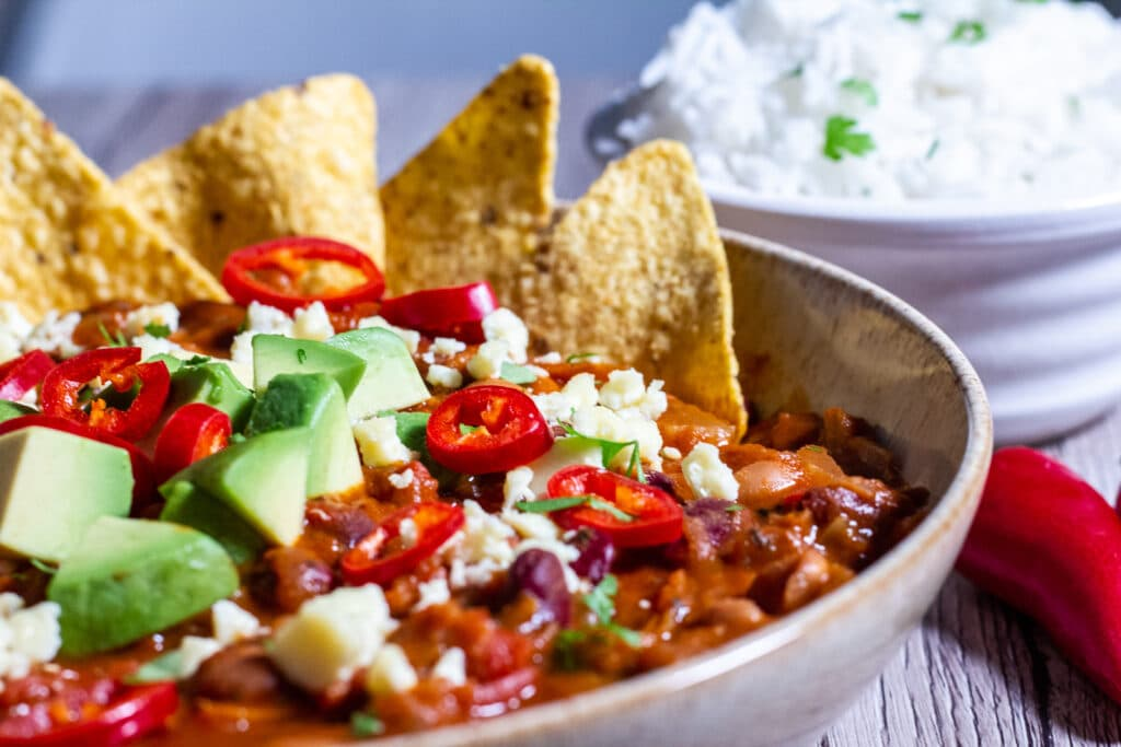 SIde view of a bowl of slow cooker bean chilli with tortilla chips and some rice.