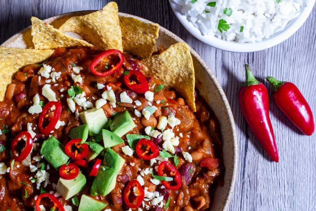 Over head view of Slow Cooker Bean Chilli with rice and tortilla chips and fresh chilli.
