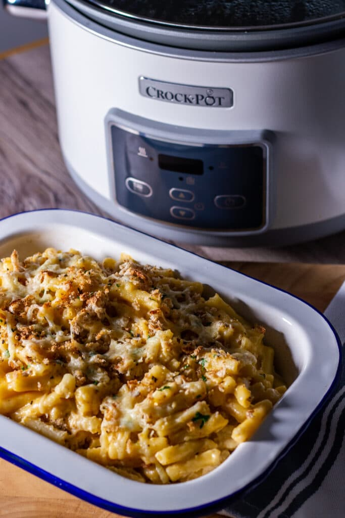 View of Slow Cooker Macaroni Cheese with Crock Pot in the background.