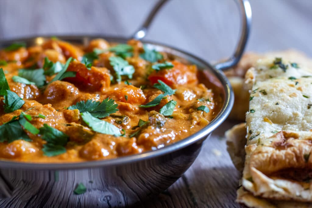 Side view of Slow Cooker and Chickpea Curry with naan bread.