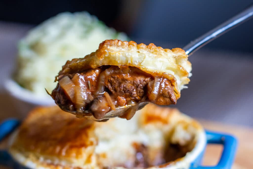 A spoon of steak pie with pastry
