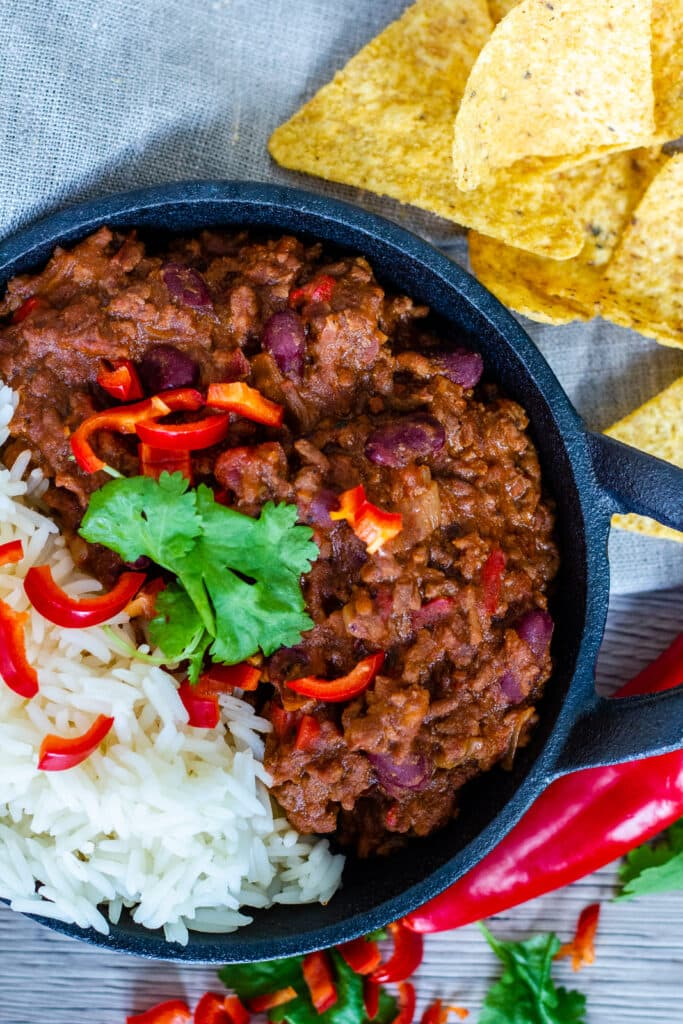 Overhead photo of Chilli con Carne, with chillis and nachos on the side