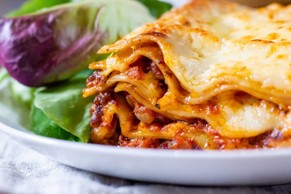 Close-up of lasagne layers next to salad