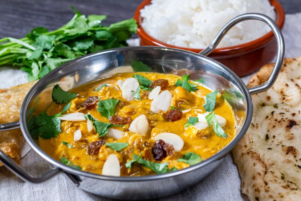 Slow Cooker Chicken Korma with rice in a terracotta bowl, bunch of coriander, samosa and naan bread