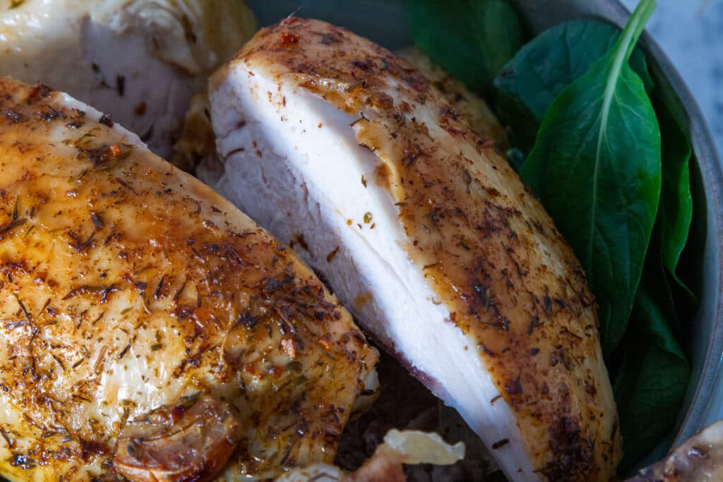 A slow cooker whole chicken, cut in two, with vegetables on the side