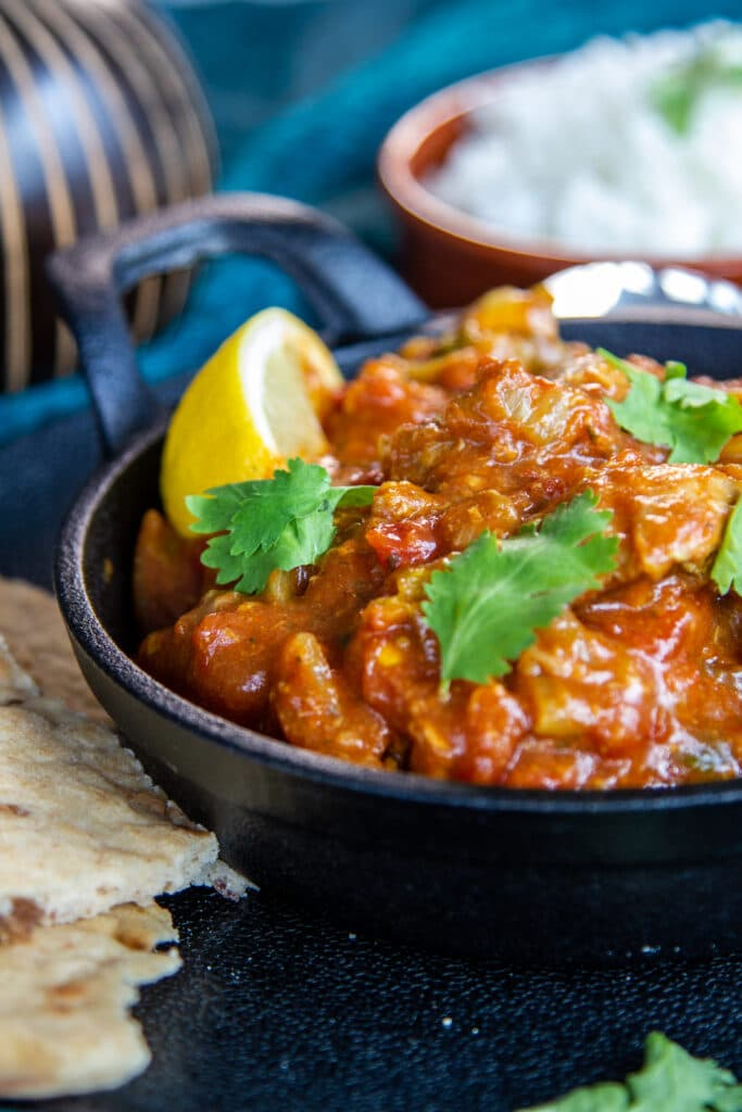 Side closeup view of a chicken bhuna, with coriander and a slice of lemon