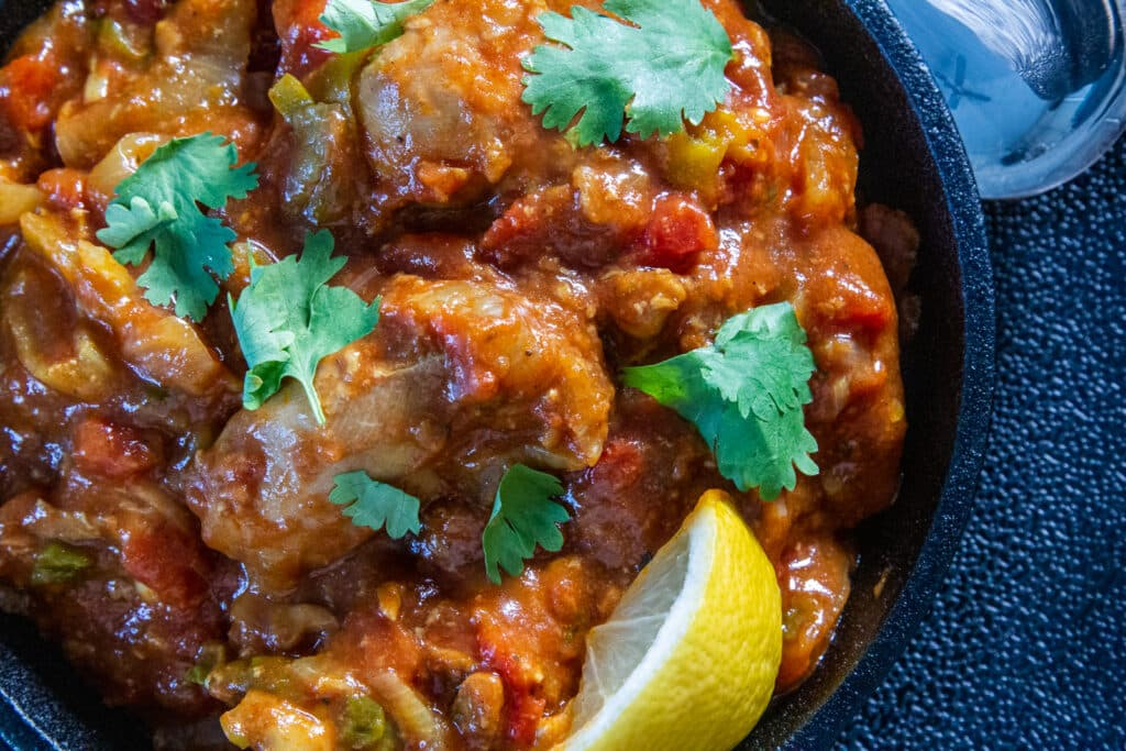 Close up view of the sauce of Slow Cooker Chicken Bhuna, topped with coriander and a slice of lemon