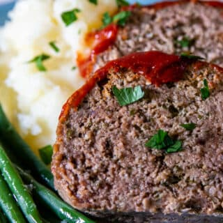 Slices of slow cooker meatloaf on a bed of mash and green beans