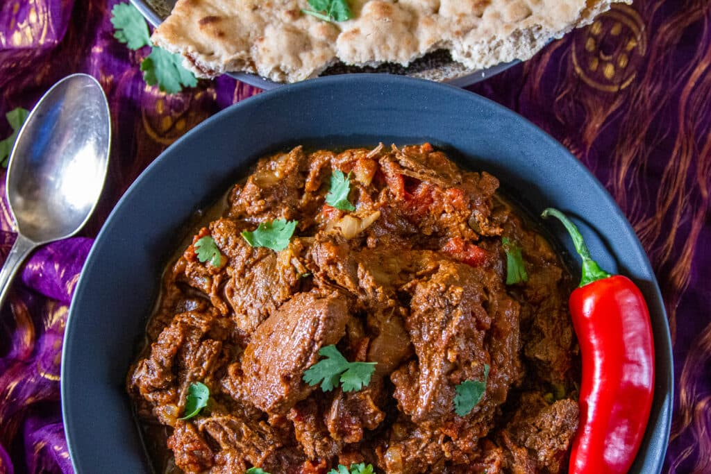 Overhead view of a bowl of Slow Cooked Beef Madras curry with chilli pepper, naan bread and tarnished spoon.