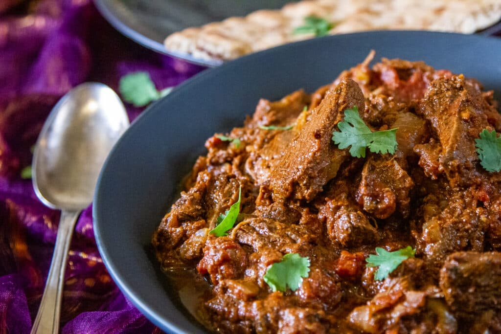 Crockpot Beef Madras curry, a tarnished spoon and a naan in the background