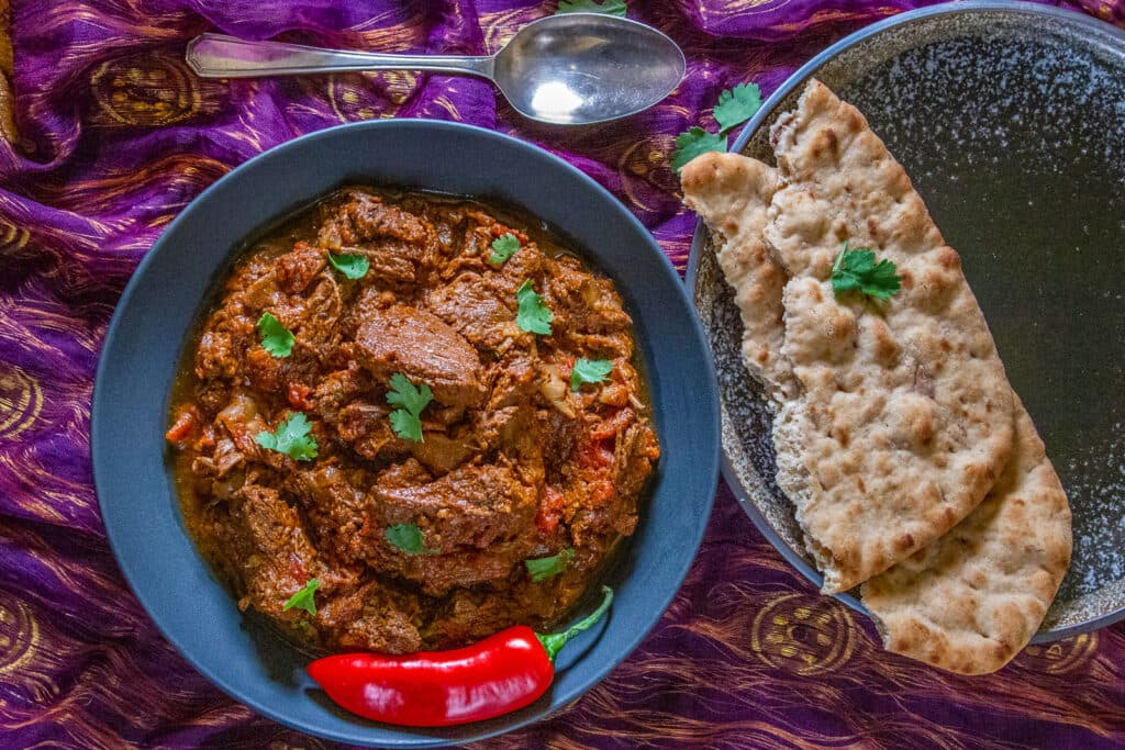 Overhead view of Slow Cooker Beef Madras and naan bread.