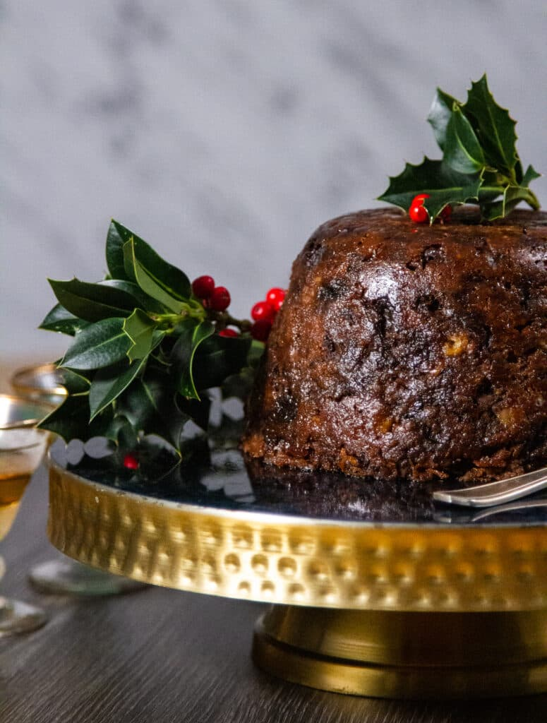 Christmas pudding on a cake stand with holly garnish