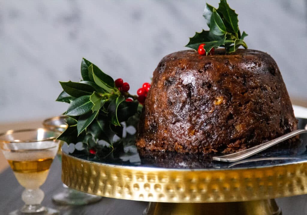 Crockpot Christmas Pudding on a gold cake stand with a glass of brandy