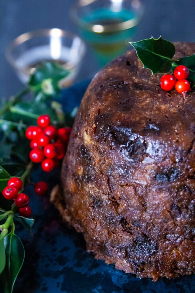 Close up view of Slow Cooker Christmas Pudding with holly and berry garnish