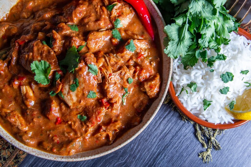 Overhead photo of slow cooker chicken curry, coriander and rice with a slice of lemon