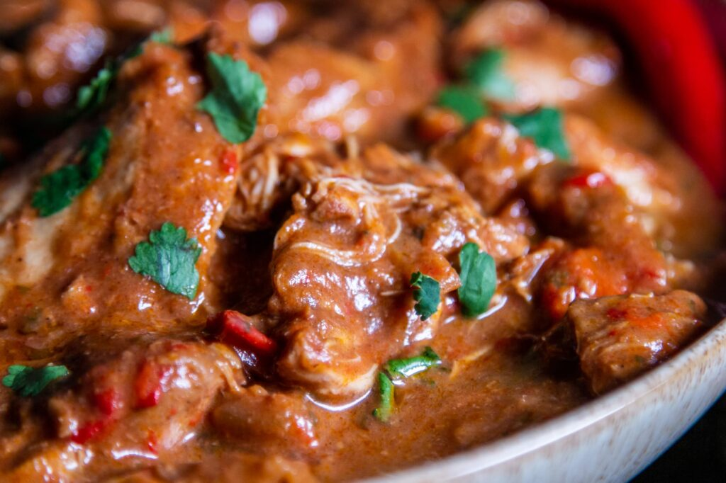 Closeup of chicken thigh in slow cooker chicken curry sauce