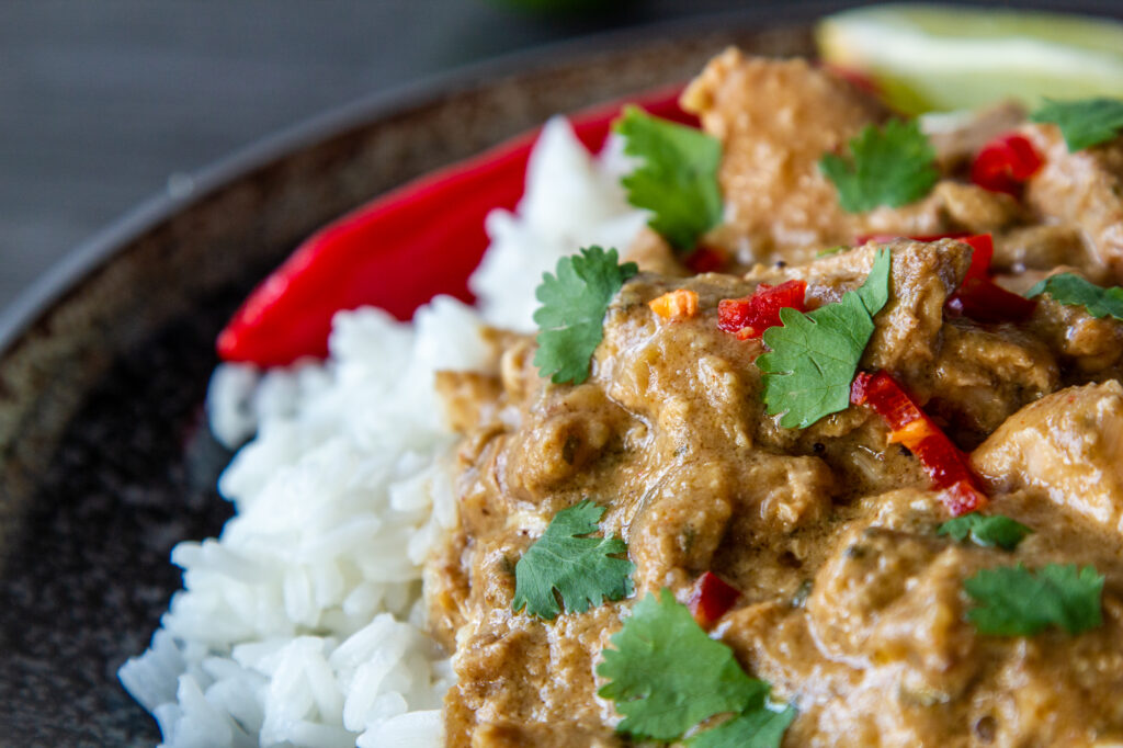 Close up view of Crock Pot Chicken Satay Curry served with rice and fresh red chilli.