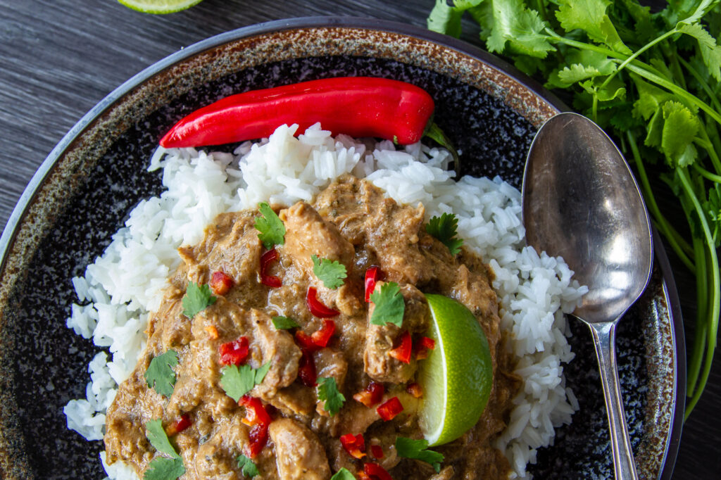 Overhead view of Slow Cooker Chicken Satay Curry on a plate with rice, lime and chilli.