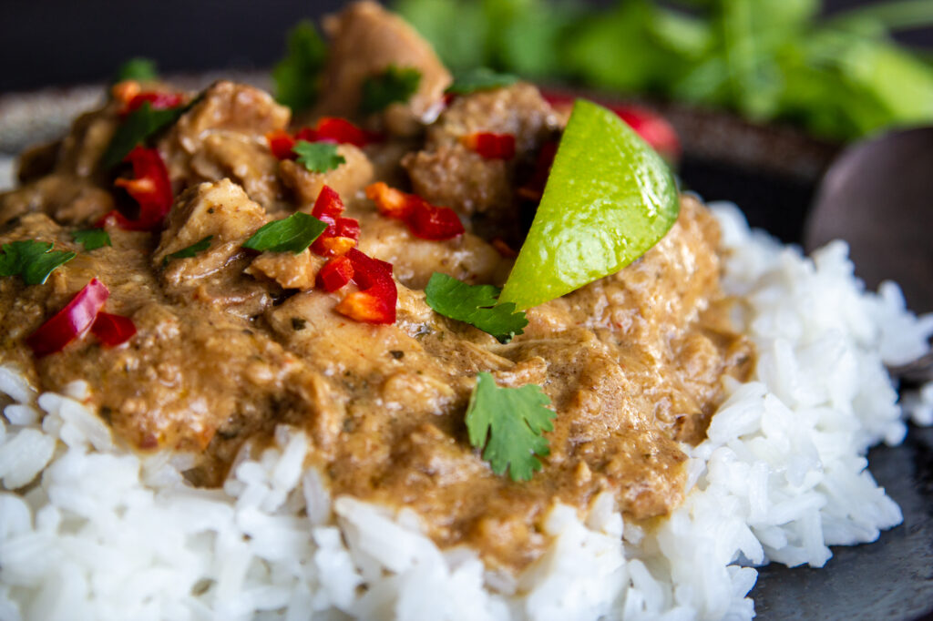 View of Chicken Satay Curry with rice, lime and chilli.