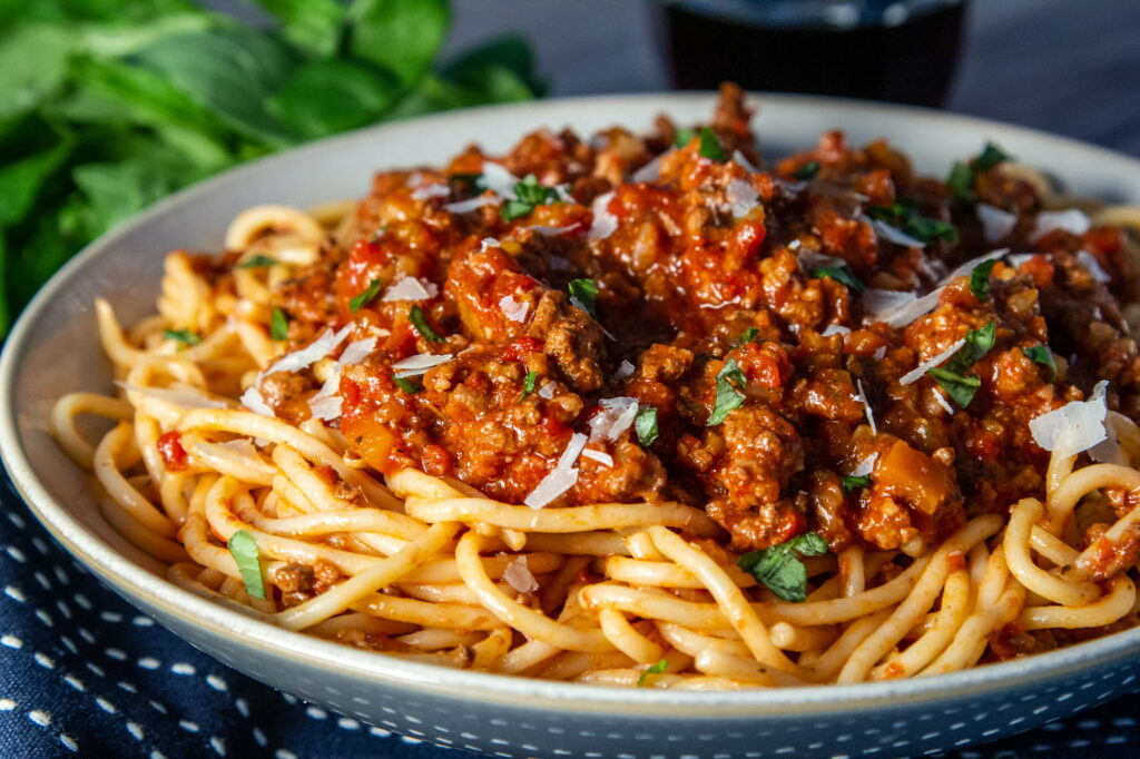 Slow Cooker Bolognese sauce on spaghetti with basil and parmesan.