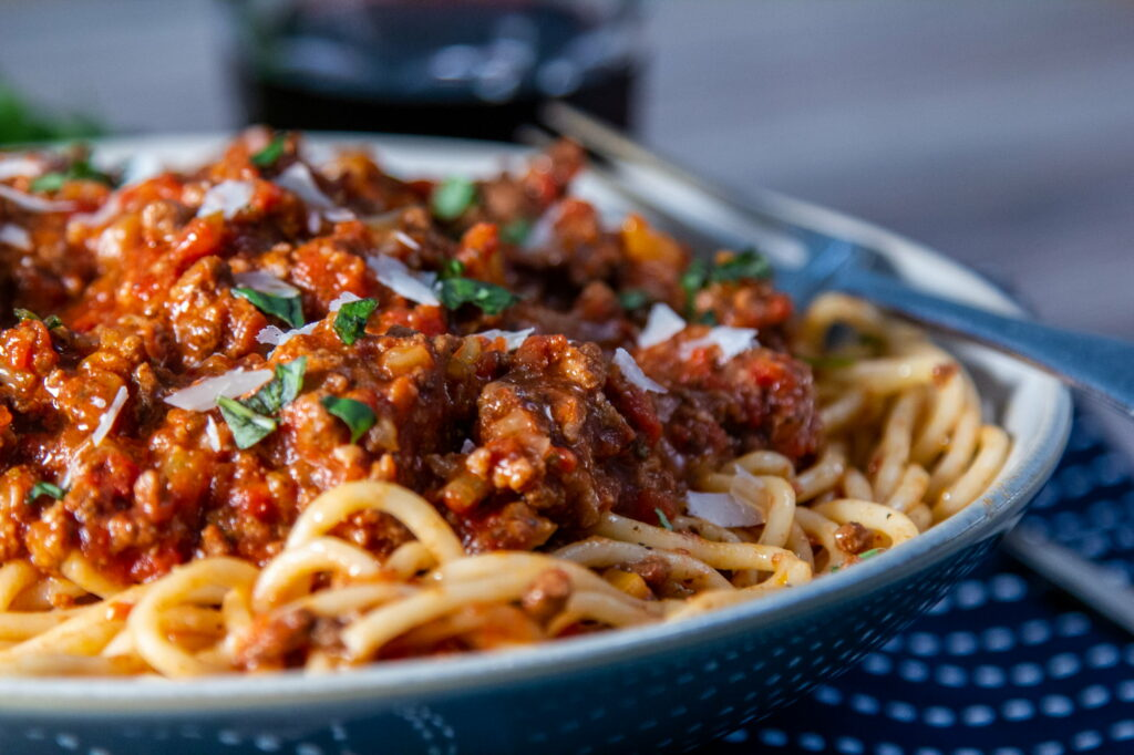 Close up view of Crock Pot Bolognese sauce with spaghetti on a plate and a fork.
