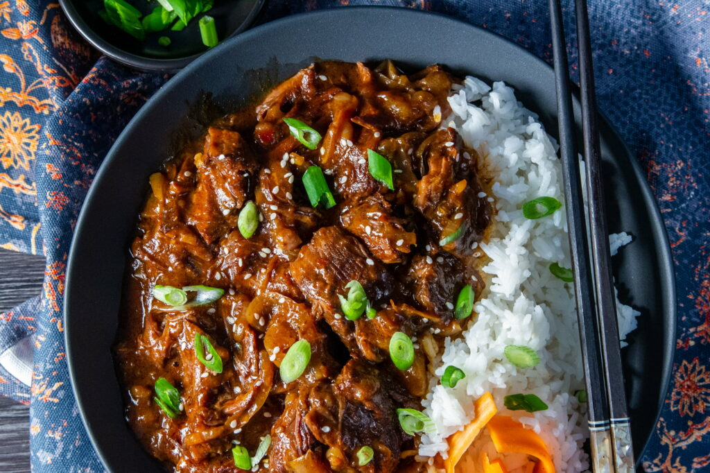 Overhead view of Slow Cooker Korean Beef in a bowl with Jasmine rice, spring onions and sesame seeds and chopsticks on the side.