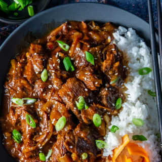 Overhead view Slow Cooker Korean Beef with Jasmine rice topped with sliced spring onion and sesame seeds.