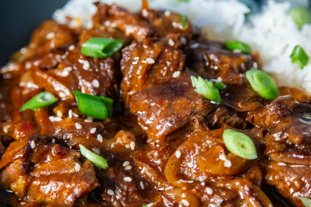Close up view of Crock Pot Korean Beef with slices of spring onion and sesame seeds sprinkled on the top and jasmine rice in the background.