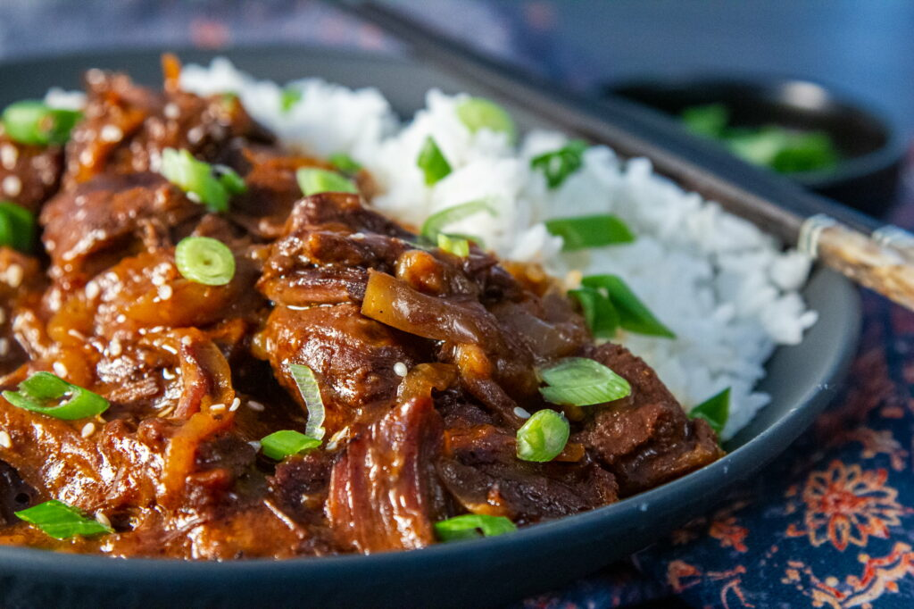 Side view of a bowl of Slow Cooker Korean Beef with Jasmine rice. Chopsticks are resting on the side of the bowl.