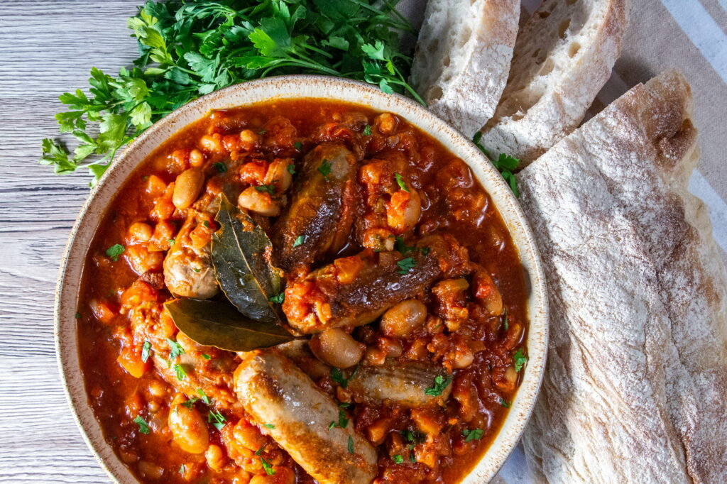 Overhead view of Crockpot Sausage Casserole with fresh parsley and crusty bread to serve.