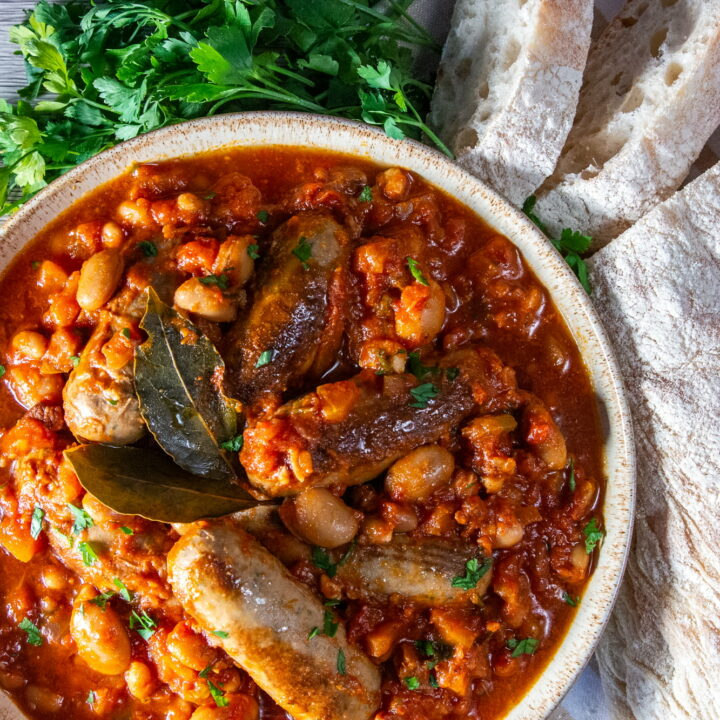 Overhead view of Slow Cooker Sausage Casserole in a bowl with fresh parsley and white crusty bread on the side.