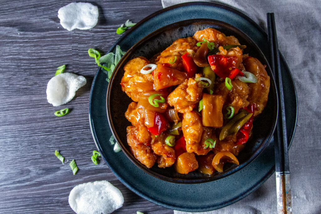 Overhead view of Crockpot Sweet and Sour Chicken with a spring onion garnish and prawn crackers on the side.