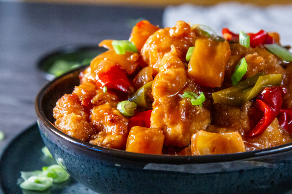 View of a bowl of Sweet and Sour Chicken with a spring onion garnish.