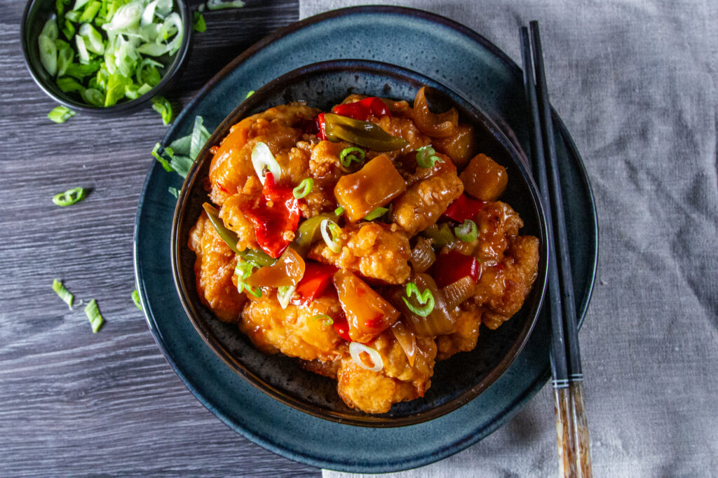 Overhead view of Slow Cooker Sweet and Sour Chicken in a bowl with a spring onion garnish and chop sticks.